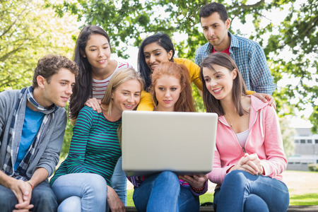 Group of young college students using laptop in the park photo