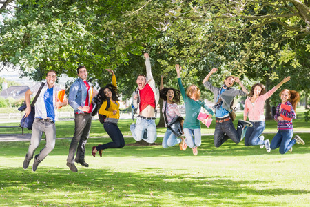 Full length of a group of college students jumping in the park photo