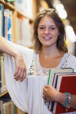 Portrait of a smiling female student standing in the library photo