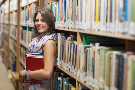 Portrait of a smiling female student leaning against bookshelf in the library photo