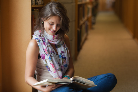 Side view of a female student sitting and reading a book in the library aisle photo