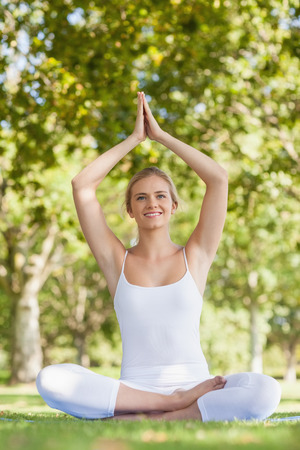 Cheerful smiling woman meditating with hands raised in prayer sitting on an exercise mat photo