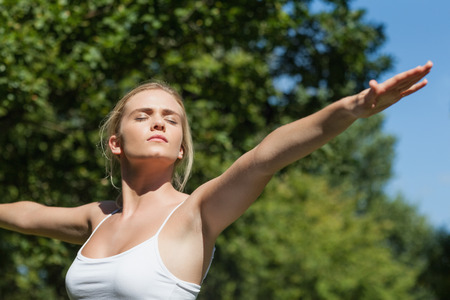 Serious peaceful woman doing yoga in a park spreading her arms photo