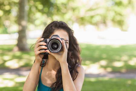 Front view of cute brunette woman taking a picture with her camera in a park photo