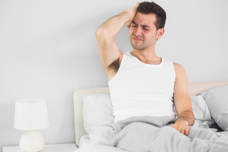 wincing: Wincing handsome man having a headache in bright bedroom