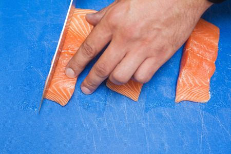 Close up of hand slicing raw salmon with sharp knife on blue cutting board photo