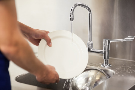porter: Kitchen porter cleaning white plates in sink in professional kitchen