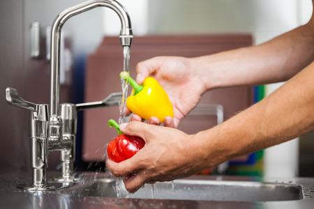 ingredients tap: Kitchen porter washing pepper under running tap in professional kitchen Stock Photo