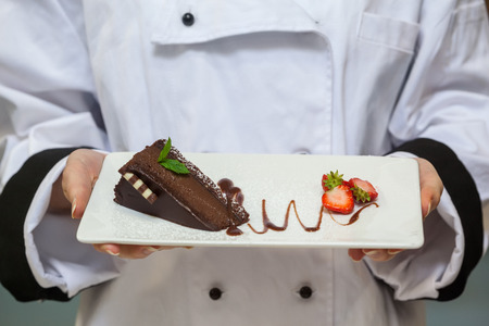 Chef presenting chocolate cake with strawberries on white plate photo