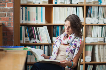 Female student sitting on chair and reading a book in the library photo