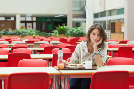 cafeteria tray: Portrait of a alone and sad female student sitting in the cafeteria with food tray