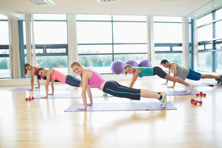 Side view portrait of trainer with class doing push ups in bright fitness studio photo