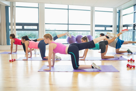 Side view of women stretching on mats at yoga class in fitness studio photo