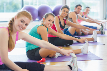 Portrait of fitness class and instructor stretching legs in bright exercise room photo