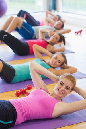 Portrait of sporty fitness class doing sit ups on exercise mats photo