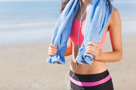 body concern: Close up mid section of a beautiful healthy woman with towel around neck standing on beach Stock Photo