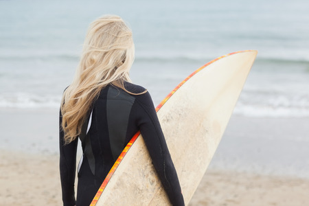 wet suit: Rear view of a young woman in wet suit holding surfboard at beach