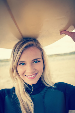 wet suit: Portrait of a smiling young woman in wet suit holding surfboard over head at beach Stock Photo
