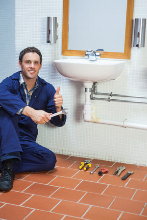 Handsome cheerful plumber sitting next to sink showing thumb up in public bathroom photo