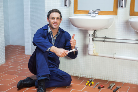 Handsome happy plumber sitting next to sink showing thumb up in public bathroom photo