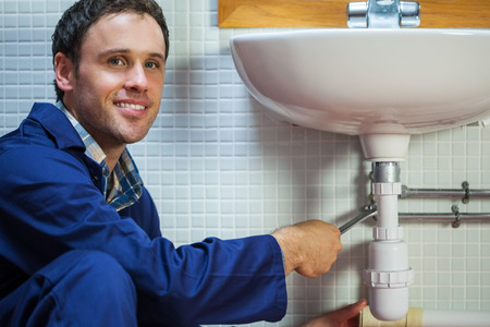 Handsome smiling plumber repairing sink in public bathroom photo