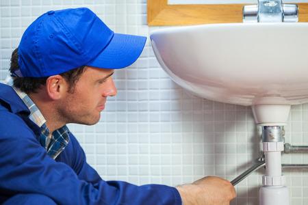 Attractive plumber repairing sink in public bathroom photo