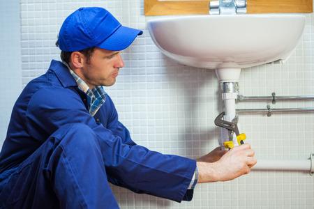 Attractive focused plumber repairing sink in public bathroom photo