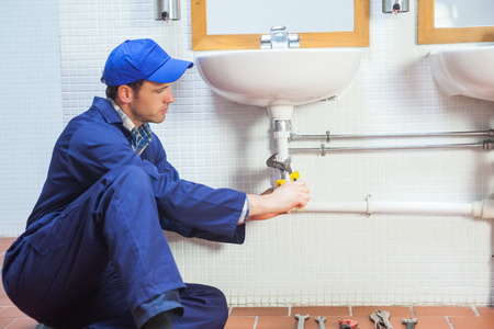 Attractive concentrating plumber repairing sink in public bathroom photo