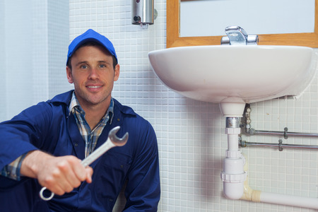 Smiling plumber holding wrench sitting next to sink in public bathroom photo