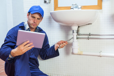 Serious plumber consulting tablet in public bathroom photo