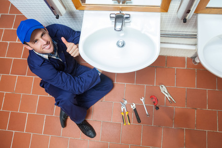 Cheerful plumber repairing sink showing thumb up in public bathroom photo
