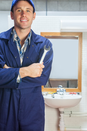 Smiling plumber posing with wrench in public bathroom photo