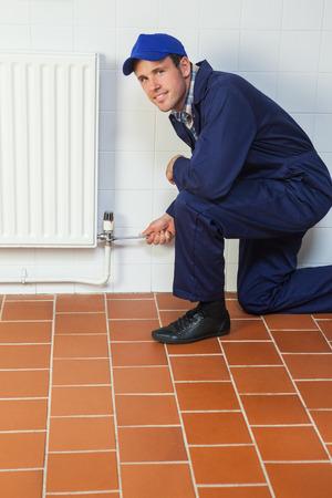 Happy handyman in blue coveralls repairing a radiator in bright room