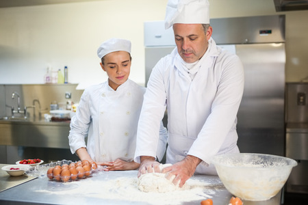 Head chef showing trainee how to prepare dough in professional kitchen photo
