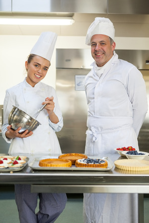 Smiling chef holding whisk while being watched by head chef in professional kitchen photo