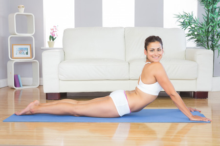 Smiling young woman stretching in a yoga pose on a blue exercise mat in her living room photo