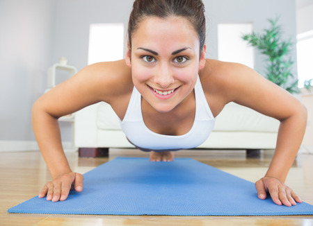 plank position: Fit young woman practicing press ups on a blue exercise mat in her living room