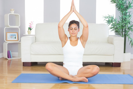 Slim brunette woman relaxing sitting in lotus position on exercise mat with hands raised in prayer photo
