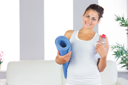 Young woman posing holding an exercise mat and a bottle in her living room smiling at camera photo