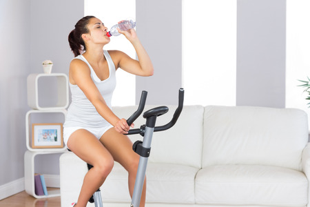Lovely slender woman drinking while training on an exercise bike in her living room at home photo