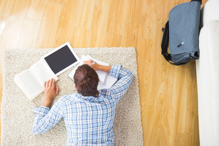 assignments: Young female student doing assignments while using her tablet and lying on the floor in the living room Stock Photo