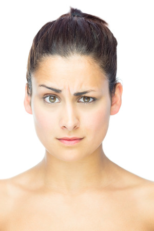 sceptical: Front view of sceptical woman looking at camera on white background Stock Photo