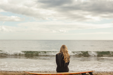 thinking woman: Rear view of a young blond in wet suit with surfboard at the beach Stock Photo