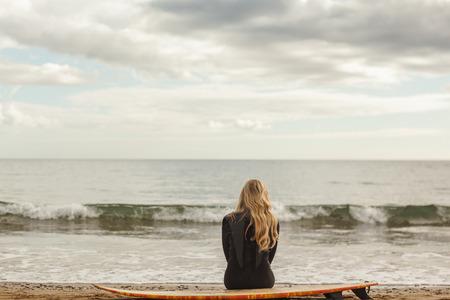 mujer pensando: Vista trasera de una joven rubia en traje de neopreno con tabla de surf en la playa