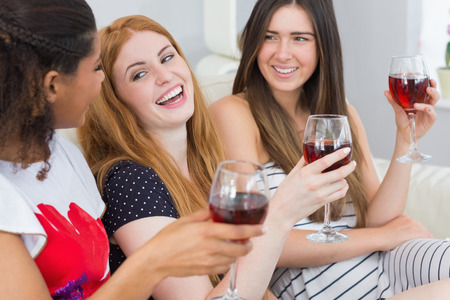 slumber: Cheerful young female friends with wine glasses enjoying a conversation on sofa at home