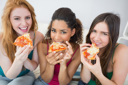 eating in: Portrait of happy young female friends eating pizza on sofa at home