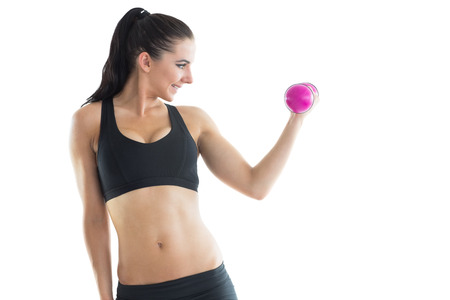 Cheerful slender woman training her arm using a pink dumbbell on white background photo