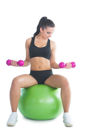 Sporty slim woman training her arms with dumbbells sitting on an exercise ball on white screen photo