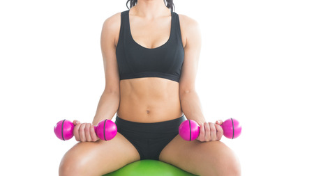 Mid section of slender fit woman training with dumbbells sitting on an exercise ball on white background photo