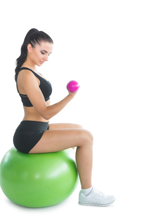 Attractive young woman sitting on an exercise ball using pink dumbbells on white screen photo